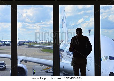 London, UK, June 14 2017. A Man Facing Window at London Heathrow Airport Waiting Area. Malaysia Airline Aircraft, Sky and Cloud at Background