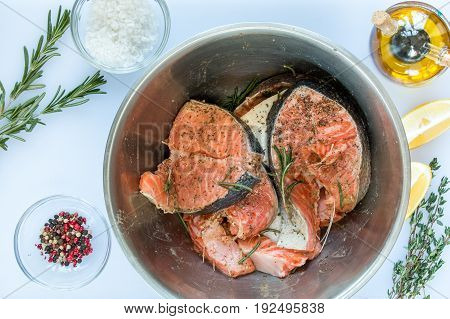 marinating steaks of salmon in stainless steel bowl sprigs of rosemary and thyme lemon pepper olive oil sea salt on a white cutting board on wooden background top view.