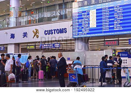 Beijing Capital Airport (PEK) Terminal 2, China, June, 14, 2017. People Waiting at Departure Gate and Customs Office.