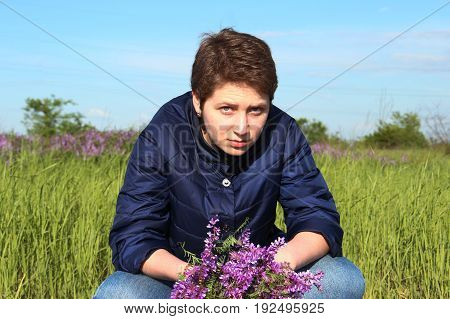 Beautiful girl sitting with her legs crossed. In the hands of a bouquet. The girl looks skeptical and serious. It does not look feminine