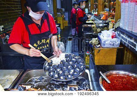 Hunan, China June 2017. A Food Stall Staff is Preparing Black Stinky Tofu at Changsha City Hunan Province China June 21 2017.