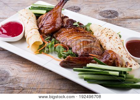Traditional chinese peking duck dish served on wooden table