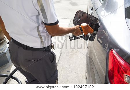 man pumping gasoline fuel in car at gas station