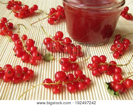 Homemade red currant jam in jar and fresh berries