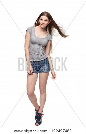 Beautiful smiling full length female in denim shorts and grey tshirt with long hair fluttering on wind, isolated on white background