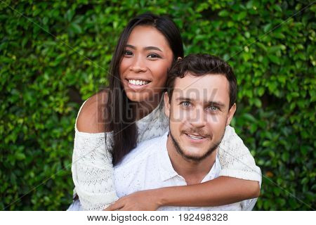 Closeup of smiling young Caucasian man piggybacking Asian girlfriend with green leaves wall in background. They are looking at camera