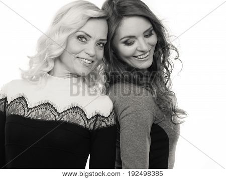 Generation and relationship. Portrait adult daughter with mother. Two attractive elegant women long curly hairs blonde mom and brown haired girl b&w photo