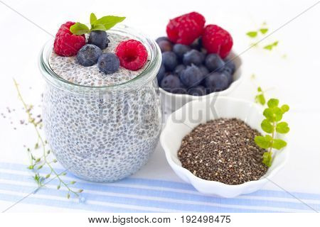 Chia seed pudding with berries in a glass jar.