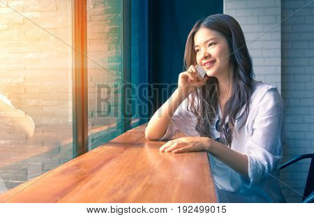 young happy asian woman using and talking on her phone at a cafe with warm light coming in from the window duo tone colors warm high light and cool blue shadow concept for communication with technology in modern lifestyle