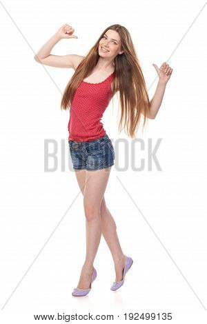 Full length of smiling leggy young female in denim shorts and red top pointing fingers at herself, isolated on white background