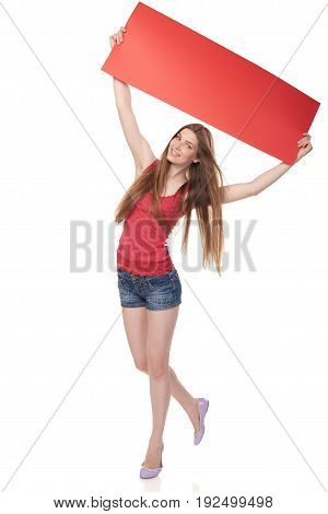 Full length young woman holding red blank cardboard over head, over white background