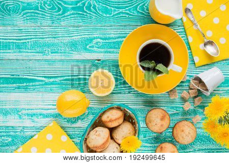 cup of black tea on yellow plate and yellow milk jug cane sugar notebook pen cakes dandelions