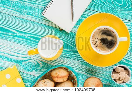 cup of coffee on yellow plate and yellow milk jug cane sugar notebook pen cakes teaspoon on turquoise colored wooden table with yellow napkin at polka dots top view