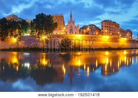 Tiber riverside with Church of the Sacred Heart of Jesus in Prati and mirror reflection during evening blue hour in Rome, Italy