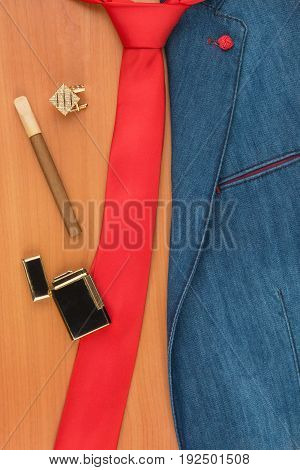 Denim jacket cufflink cigar and lighter lying on a wooden surface with space for your text. View from above