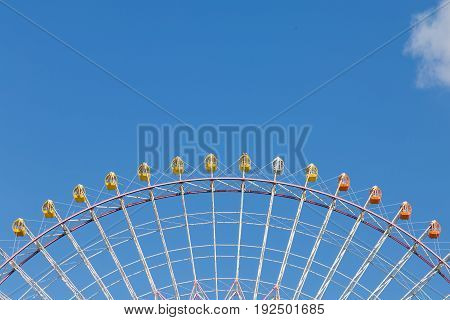 Top half of big funfair ferris wheel amusement festival outdoor with clear blue sky background