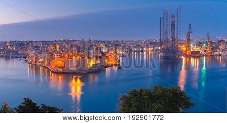 Panoramic aerial skyline view of ancient defences of Three cities, three fortified cities of Birgu, Senglea and Cospicua and Grand Harbor with ships, as seen from Valletta during morning blue hour, Malta.