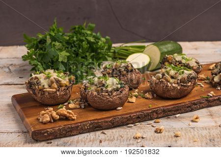 Mushroom caps stuffed with vegetables and cheese baked in oven and garnished with a sprig of parsley. Mushroom appetizer on wooden board. Closeup