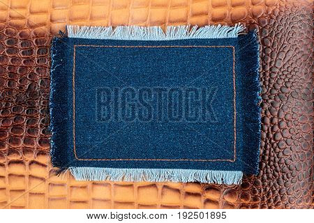 Frame made of denim with a fringe is on the brown crocodile skin with space for your text. View from above