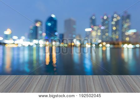 Opening wooden floor Twilight blurred bokeh office building with water reflection at night abstract background