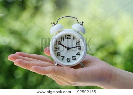 Closed up of white alarm clock in woman hand as business or time countdown concept with green bokeh in summer sun shine.