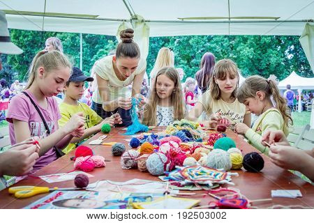 Zaporizhia/Ukraine- May 28, 2017: Charity Family festival- young woman - volunteer explaining to girls how to knit colorful table napkins at  art and craft workshop, outdoors children activity