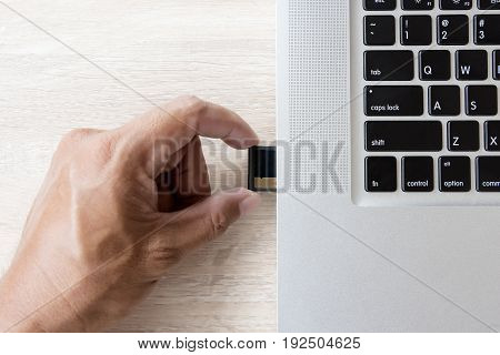 hand inserting memory card into laptop slot