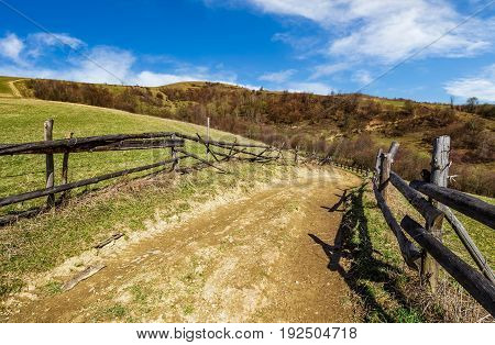 wooden fence by the road in rural area. springtime countryside landscape in mountains with grassy meadows. beautiful sunny weather