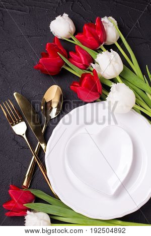 Festive table setting. White plate golden cutlery and white and red tulips flowers on black textured backgroud. Selective focus. Top view.