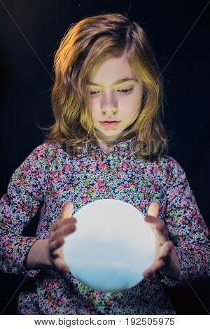 Little girl holding in hands a ball of light