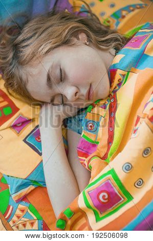 Portrait of little girl lying in her bed