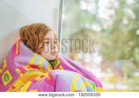 Wrapped in a blanket little girl sitting on the windowsill