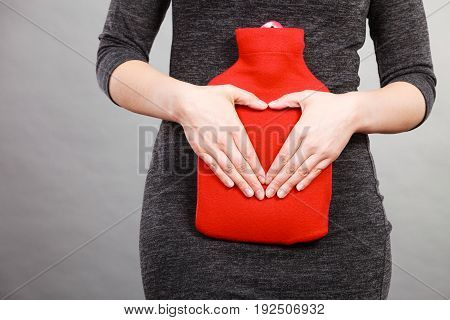 Unrecognizable woman having stomach ache holding hot red water bottle on abdomen as remedy for pain making heart shape by hands. Health care.