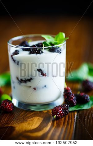 Sweet Greek yogurt with mulberry berries on a wooden table