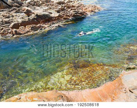 Woman swimming in crystal clear water in Canal Rocks Western Australia
