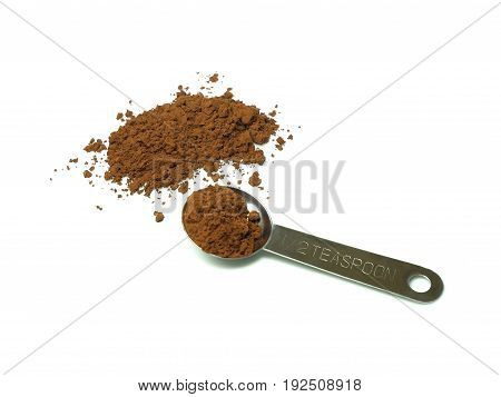 Cocoa powder and measuring spoon isolated on white background