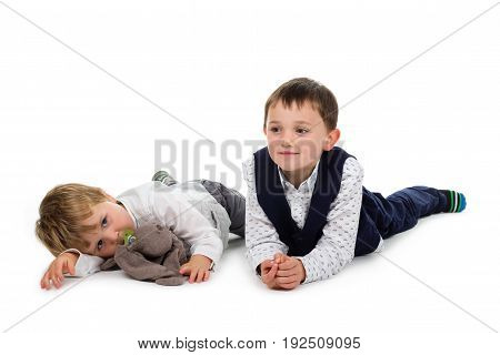 2 Little brothers wearing festive clothing lying on the ground with plush animal (rabbit) and pacifier. Isolated on white background