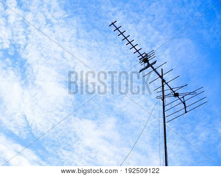 Silhouette TV antenna on cirrocumulus clouds and blue skies