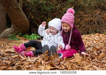 Little Sisters Playing In The Leaves