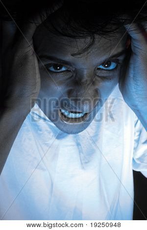A portrait of a stressed Indian man in dramatic lighting. poster