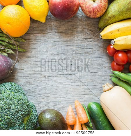 Different fruits vegetables arranged in a circle, top view on the grey table selective focus