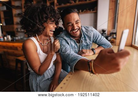 Laughing young couple sitting together at coffee shop and taking selfie using smart phone. Young man with his girlfriend taking self portrait and smiling.