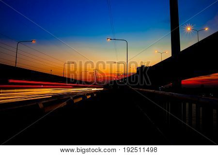 Abstract of beautiful car lights on the road and bridge in the rush hour with beautiful sunlight background