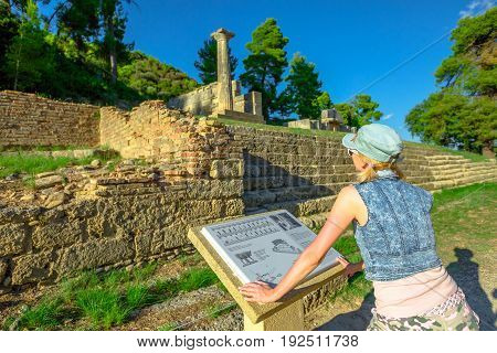 Tourist woman reading explanation of popular Archaeological Site. Mediterranean travel destination. Young traveler visiting Ancient Olympia in Peloponnese, Greece. Female tourist in Unesco Heritage.