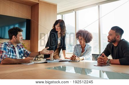 Indoor shot of young creative business people in a meeting in conference room. Multiracial group of people sitting around a table and discussing new business ideas.