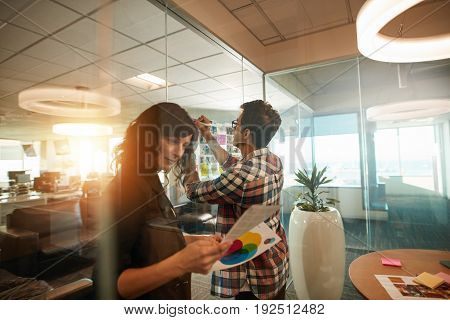Two creative professionals working on new project. Woman looking at photographs and man sticking at paper on glass wall in office.
