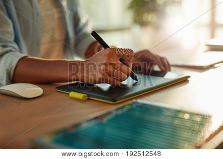 Closeup of woman's hand using a graphic tablet and stylus pen. Female designer working at her desk