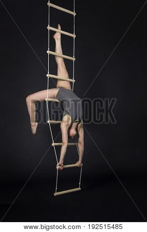 Young,smiling Girl Performs Gymnastic Exercises On A Rope Ladder.