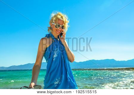 Summer holidays. Happy woman talking on a smartphon on tropical beach. Blonde beach woman wearing an blue sarong and sunglasses enjoying. Turquoise sea of famous Elafonisos island, Greece, behind her.