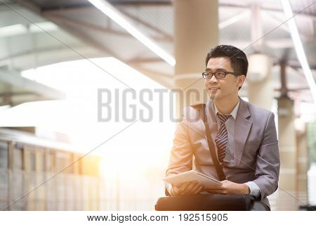 Asian businessman using digital tablet pc at commuter station, with beautiful sun flare at background.